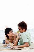 beautiful young asian couple having fun with apple