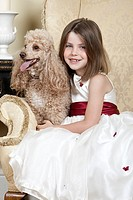 Shot of a Happy Blonde Girl in Large Armchair with an Apricot French Miniature Poodle