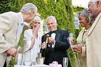 Well_dressed senior couples opening champagne bottle