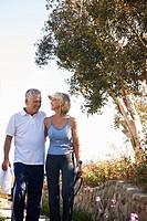 Smiling senior couple walking with tennis racket