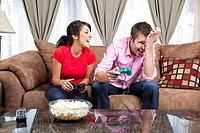 Couple sitting on sofa and playing video game
