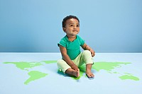 Baby boy sitting on world map on floor