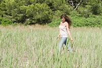 Young woman walking through field