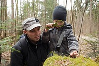 Father and son using loupe