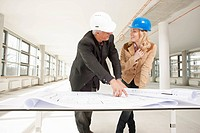 Two architects checking plans of site
