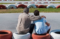 Hispanic grandfather and grandson on go_cart track
