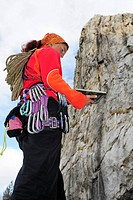 Woman with climbing gear and climbing rope reading a guidebook, Massa, Tuscany, Italy