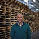 Black man standing near wooden pallets in warehouse