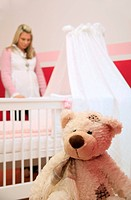 Pregnant woman standing at baby crib with teddy in foreground