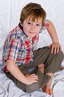 child sitting on the floor with legs crossed
