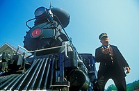 A steam engine conductor checks the time as he stands near the cowcatcher on the front, Eureka Springs, Arkansas
