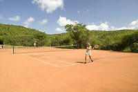 A tourist couple enjoy a game of outdoor tennis at Lewa Downs in North Kenya, Africa. Tourism has taken a significant leap forward for local communiti...