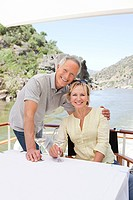 Senior couple with glasses of wine on a boat holiday
