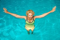 senior woman doing aquagym in a swimming pool