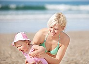 Smiling mother at the beach with her daughter in the sun