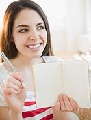 Brunette woman holding an empty notebook
