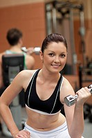 Portrait of an attractive woman working out with dumbbells in a fitness center