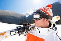 Skier carrying skis through snow