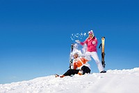 Couple with skis having snowball fight in snow