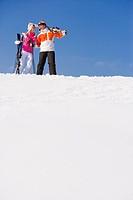 Couple carrying skis through snow