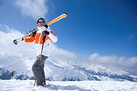 Skier on remote mountain top carrying skis