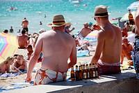 German boys drinking at the beach , palma de mallorca