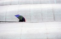 Spectator at a tennis tournament walks between covered courts