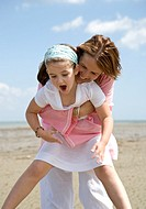 Mother lifting and embracing daughter laughing and screaming