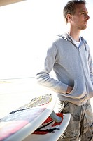 Young man looking into the distance standing by surfboards