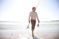 Man holding fish and fishing rod walking on a beach