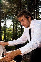 Close up of a businessman sitting in park reading a newspaper