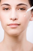 Close up of a young woman applying an anti-aging serum on her face with a dropper