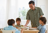 Father serving dinner to sons at table