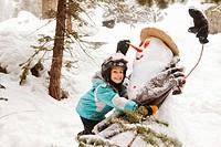 Smiling girl hugging snowman