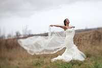 ontario, canada, a bride standing in a field holding out her veil in the wind