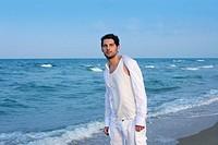 Latin young man white shirt walking on blue beach outdoor