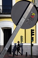 WOMAN WALKING ON THE STREET UNDER A LEANING SIGN, PASEO DE RECOLETOS, MADRID, SPAIN