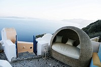 A sofa on an open rooftop with the view of the sea