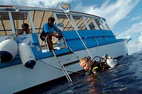 One scuba diver climbing aboard a diving boat, Kaafu Atoll, Maldive Islands.