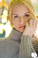 Portrait of serious young blonde woman in grey sweater