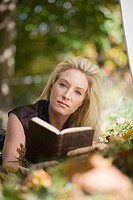 Portrait of blonde woman lying outdoors with book