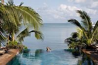 Thailand, Koh Samui. Thai Woman bathing in swimming pool next to sea ...