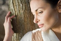 Close_up of a young woman by a tree trunk in the field