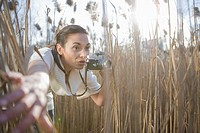 Curious young woman with camera in field