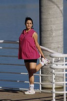 Pregnant woman exercising outdoors ...