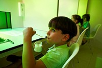 Children tutored by a sensory analysis specialist during a yoghurt tasting session with green lights to disguise the yoghurt colour, AZTI-Tecnalia Mar...