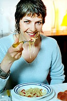 Woman over forty eating pasta