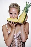 Woman´s portrait biting a pineapple