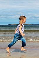 girl running on sandy beach, Sutherland, Scotland