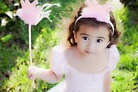 Little girl playing dress up as a princess.